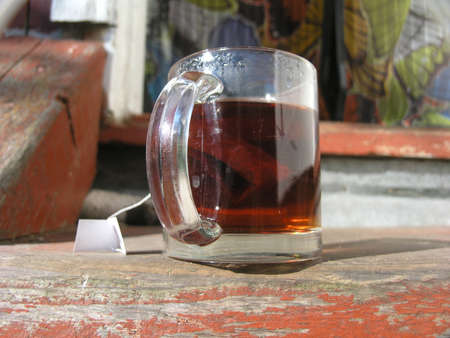 Transparent mug of tea placed on a doorway wooden step, macro shot