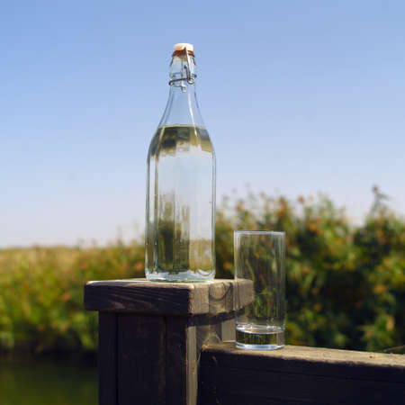 A bottle of water and a glass placed on a handrail, outdoor closeup