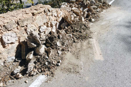 A road fence made of rocks partly damaged after a car acident