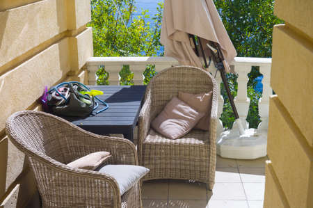 Sun umbrella nad armchairs in a patio or balcony, sunny day shot Stock Photo - 156629920