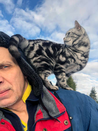 Cropped shot of a man walking with a cat on his back, winter scene