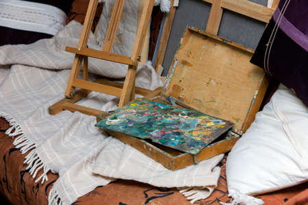 Interior with a unmade sofa with artistic equipment left on the blanket