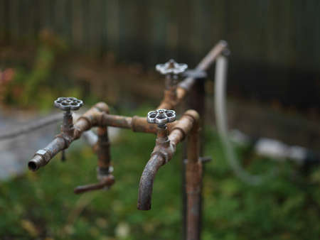 Old metal rusty water supply pipes and taps, shallow dof