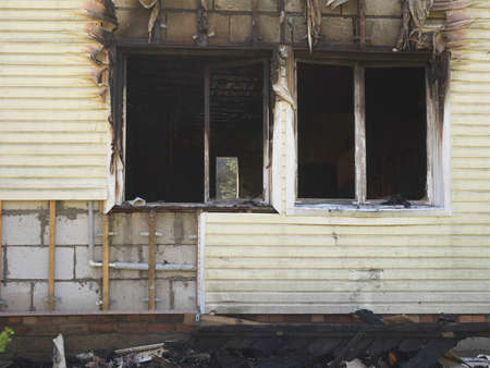 facade of a house after fire with empty windows and damaged facade