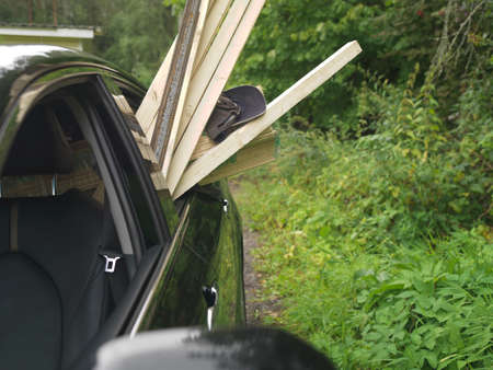 A car with long planks sticking out of the window, outdoor shot Stock Photo