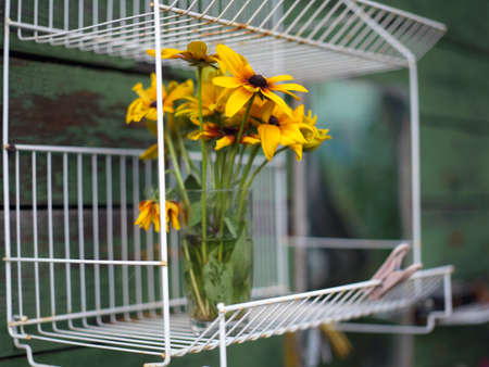 Yellow daisy bouquet placed in a glass on the steel shelf Stock Photo - 157884567