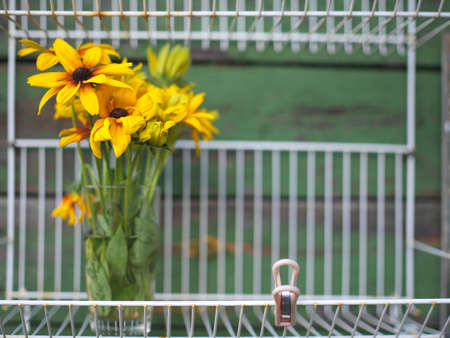Yellow daisy bouquet placed in a glass on the steel shelf, outdoor front shot Stock Photo - 157884254