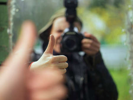 Reflection of a photographer in a mirror gesturing okay sign while shooting, shallow dof