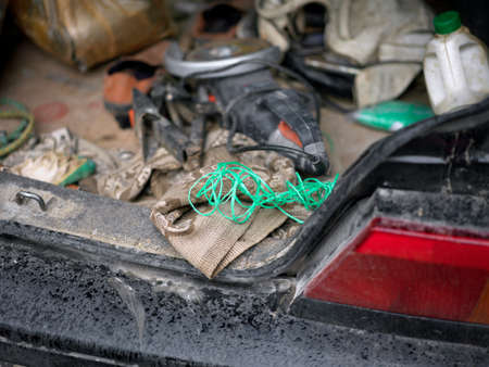 Open messy car trunk with handtools, outdoor closeup