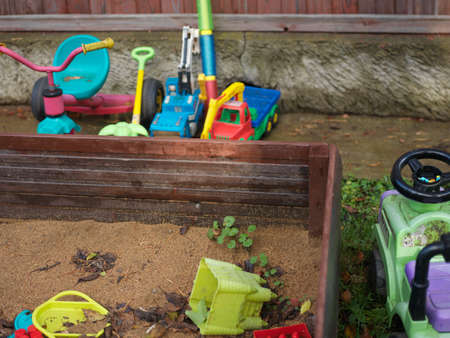 Playground with a sandbox and abandoned toys, outdoor shot