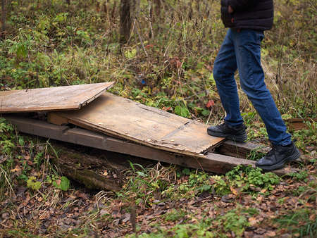 A man wearing sport boots and jeans crossing a ditch