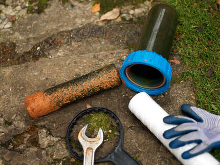 Replecement of used water filter, a new one and wrench with glove dropped on the ground