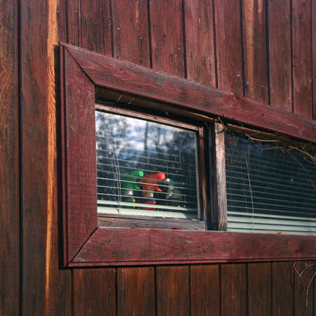 A wooden house window with blinds and household stuff, outdoor cropped image