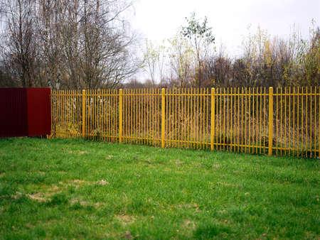 Yellow metal fence, a daytime autumn shot