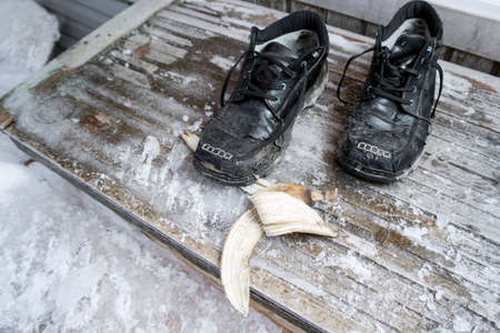 Banana skin on the slippery steps and a foot wear, outdoor closeup 版權商用圖片