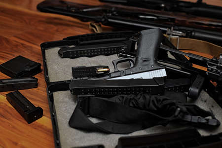 Pile of firearms dropped on the wooden floor, indoor close-up