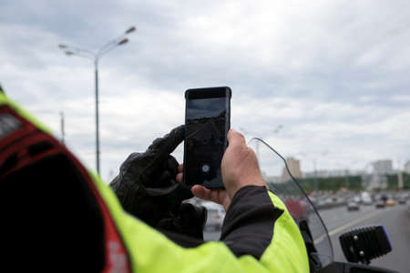 traffic police officer taking a picture of traffic on mobile phone 版權商用圖片