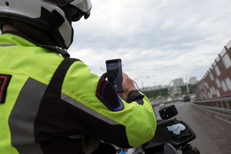 Road police officer sitting on a bike and taking photo of traffic