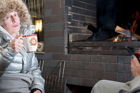 a woman wearing hood drinking hot drinks in front of the fireplace, night scene