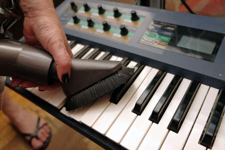 Dust removing from a synthesizer keyboard with a vacuum cleaner