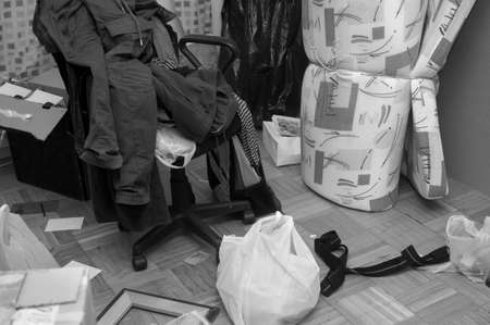 messy room interior with a pile of clothing on a chair and household stuff scattered on the floor, in black and white 版權商用圖片