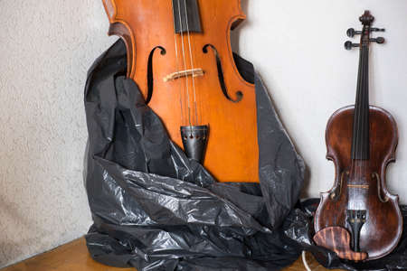 Cello and violin seemingly need repar and placed in a room corner