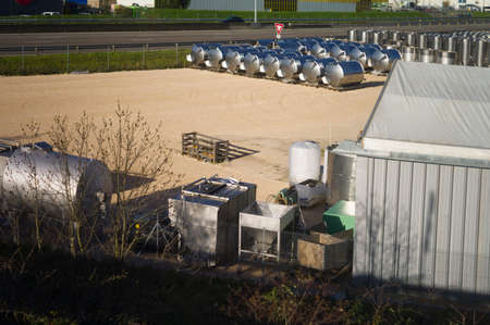 A landscape with a fenced area and steel storage tanks
