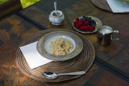 Porridge with berries and cream on the set table, outdoor closeup
