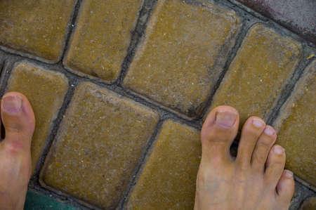 overhead shot of bare feet standing on the tiled floor