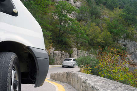 sharp turn in mountains and a vehicle with bad tire in the foreground