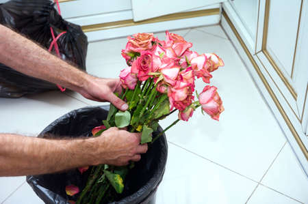 male hands throwing a rose bouquet into a garbage bin, concept of end of love, shallow DOF 版權商用圖片