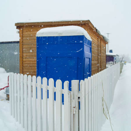 PVC transportable public toilet behind the fence, focus in the foreground, winter scene Standard-Bild