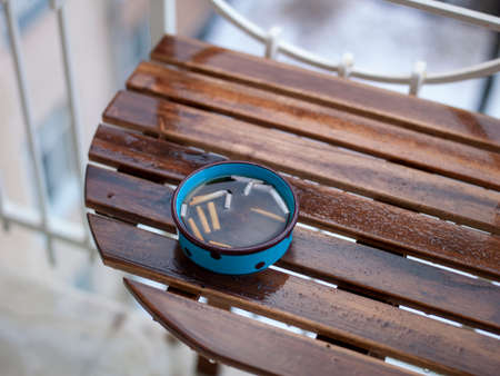 Ashtray full of water placed on a wet wooden table top, outdoor closeup, shallow DOF Stock Photo