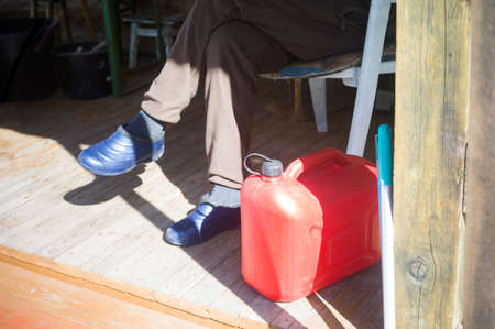 A man sitting outdoor next to red fuel jerrycan
