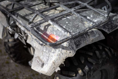 rear of a quadbike covered with dry mud, shallow DOF outdoor shot