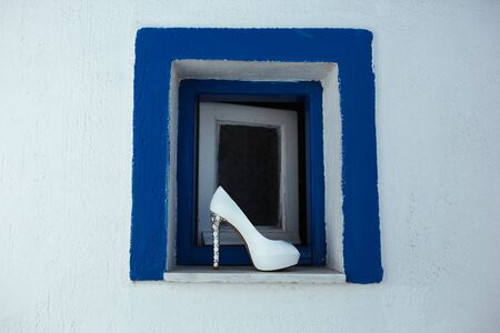 one female white shoe stands on a small window with a blue border