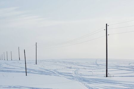 Snow field crossed by tracks from passing cars and poles