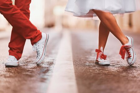 Newlyweds in sneakers are standing on the street. They crossed their legs.