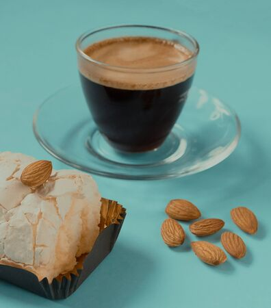 A glass Cup of black coffee with merinque cake and almond. Beautiful breakfast.