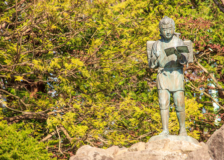 the statue of Ninomiya Sontoku (born - Ninomiya Kinjiro), showing him as a boy reading a book while walking and carrying firewood on his back, representing good virtues, hardworking and perseverence Foto de archivo