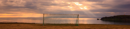 a goal with sunlight shining through clouds at dawn as a background. Concepts of making lots of effort and the hope will become true, mood changes to positive, energy, warmth, vitality, belief in own self.