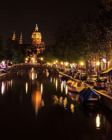 View of a church and a canal in Amsterdam, Netherlands at night. The Basilica of Saint Nicholas (Sint-Nicolaasbasiliek) with the reflection in the canal