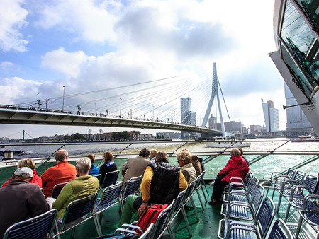 ROTTERDAM, NETHERLANDS - SEP 03, 2016: Tourists on the Spido boat tours looking up Erasmus Bridge in Rotterdam. It offers tours around one of the largest ports in the world It operates for over 80 years and has over 400,000 passengers per year. Editorial
