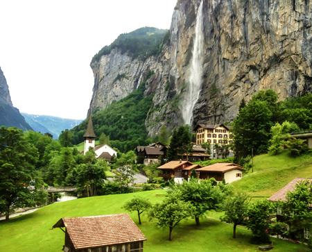 Beautiful Staubbachfall waterfall flowing down the picturesque Lauterbrunnen valley and village in Bern canton, Switzerland, Europe
