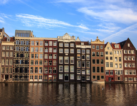 Beautiful traditional old buildings at day with bright blue sky in Amsterdam, the Netherlands
