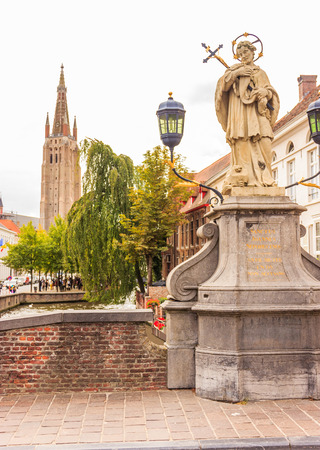 Peace of mind moment off the busy tourist crowd at Sanctus Joannes Nepomucenus statue, Bruges, Belgium, Europe.