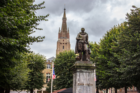 Simon Stevin Bronze Statue in Bruges with park and church as background, Bruges, Belgium, Europe.