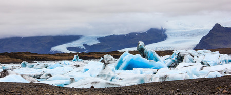 Stunning winter day view of Jokulsarlon, glacial river lagoon, large glacial lake, southeast Iceland, on the edge of Vatnaj�kull National Park, one of the natural wonders of Iceland. The large luminous blue iceberg resembling ghostly knight riding horses