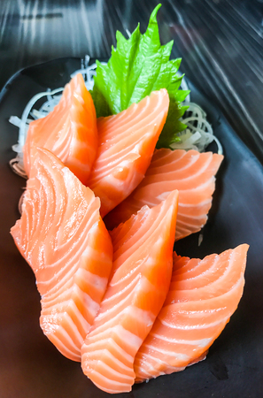 Japanese food: salmon sashimi (fresh raw salmon meat) decorated with grated turnip and mint leaf on wooden table as a background.