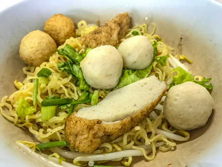 Asian Street Food. Closeup Egg noodle with varieties of fish meatballs. Stock Photo